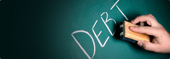 "The word ""DEBT"" written on a chalkboard with an eraser coming to erase it."