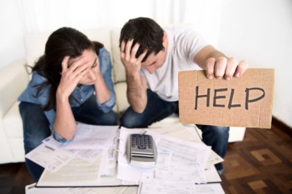 "A concerned and stressed out looking couple sit with paperwork and a calculator holding up a cardboard ""Help"" sign."