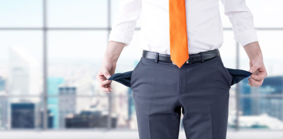 A business man pulling his pant pockets inside out to show there is nothing in them.