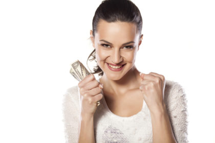 a woman excited because she has a fist full of money